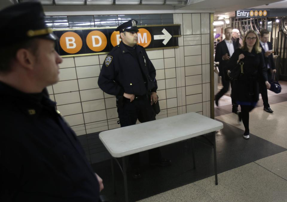 Police officers keep an eye on commuters in a subway station in New York, Tuesday, April 16, 2013. Police armed with rifles and extra patrol cars were stationed around the city Tuesday as New York remained in a heightened state of alert until more is known about the bombings at the Boston Marathon. (AP Photo/Seth Wenig)