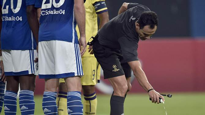 Referee Carlos Velasco Carballo from Spain makes use of foam spray during the Champions League group G soccer match between FC Schalke 04 and Maribor in Gelsenkirchen, Germany, Tuesday, Sept. 30, 2014