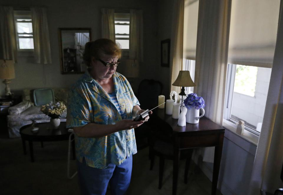 Susan Slowik tunes a battery-operated television in her living room in Baltimore, Tuesday, July 3, 2012, as she awaits the return of electricity for the first time since last weekend's severe storms. (AP Photo/Patrick Semansky)