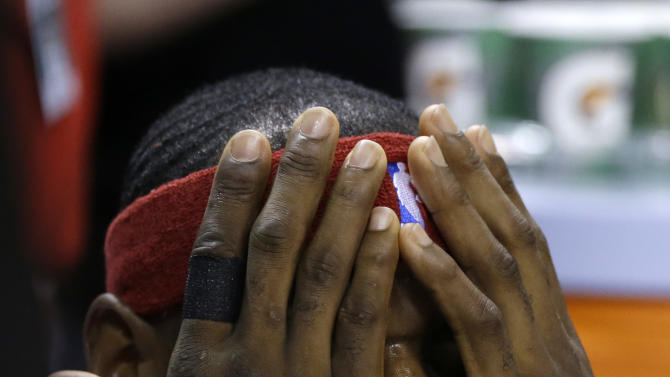 Cleveland Cavaliers forward LeBron James covers his face while sitting on the bench before an NBA basketball game against the Miami Heat, Thursday, Dec. 25, 2014, in Miami. (AP Photo/Lynne Sladky)