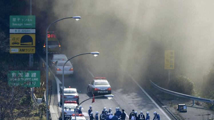 Police vehicles are parked at the entrance as smoke billows out of the Sasago Tunnel on the Chuo Expressway in Koshu, Yamanashi Prefecture, central Japan, Sunday morning, Dec. 2, 2012. A part of the tunnel collapsed Sunday morning, possibly involving several vehicles and injuring several people, local media said. (AP Photo/Kyodo News) JAPAN OUT, MANDATORY CREDIT, NO LICENSING IN CHINA, FRANCE, HONG KONG, JAPAN AND SOUTH KOREA