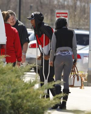 Louisville basketball player Kevin Ware, center, walks to the back doors of the Yum! Center to be reunited with his teammates, Tuesday, April 2, 2013, in Louisville, Ky. Ware was back on campus Tuesday afternoon after he had been released from an Indianapolis hospital, two days after breaking his right leg during the Cardinals' Final Four-clinching victory. (AP Photo/The Courier-Journal, John Sommers II) NO SALES; MAGS OUT; NO ARCHIVE; MANDATORY CREDIT