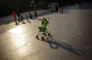 A baby stroller is seen as mothers play with their children at a public area in downtown Shanghai