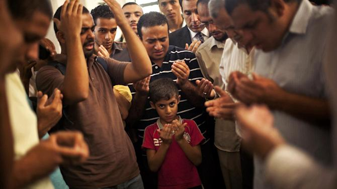 A son of the late Ammar Badie prays during his father's funeral in al-Hamed mosque in Cairo's Katameya district on Sunday, Aug. 18, 2013. Badie, the son of Muslim Brotherhood's spiritual leader Mohammed Badie, was killed by Egyptian security forces Friday during clashes in Cairo's Ramses Square. Egypt's military leader vowed Sunday that the army will not allow further violence after the deaths of hundreds in days of political unrest, while still calling for the political inclusion of Islamist supporters of the country's ousted president. (AP Photo/Manu Brabo)