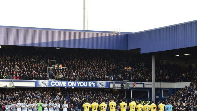 Queens Park Rangers and Crystal Palace players stand as a mark of respect to passengers on the missing AirAsia Flight QZ8501 ahead of their English Premier League soccer match at Loftus Road in London
