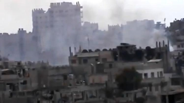 This image taken from video obtained from the Shaam News Network, which has been authenticated based on its contents and other AP reporting on Wednesday, Oct. 10, 2012, shows smoke rising from buildings due to shelling in Homs, Syria, on Tuesday, Oct. 9, 2012. (AP Photo/Shaam News Network via AP video)