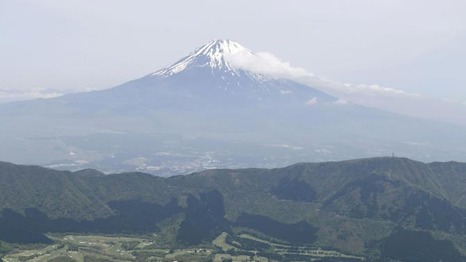 Owakudani valley, a popular tourist spot on Mt. Hakone, is seen in front of Mt. Fuji in Hakone