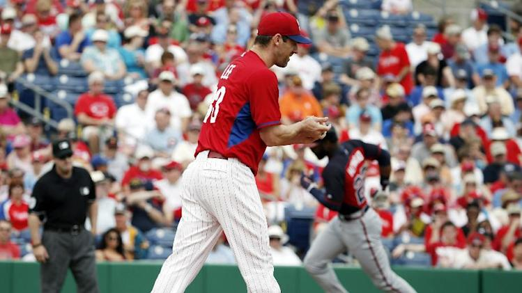 Philadelphia Phillies starting pitcher Cliff Lee reacts as Atlanta Braves right fielder Jason Heyward trots the bases after hitting a first-inning solo home run off Lee in a spring exhibition baseball game in Clearwater, Fla., Monday, March 10, 2014