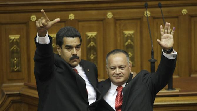 Venezuela's President-elect Nicolas Maduro, left, and National Assembly President Diosdado Cabello wave during Maduro's inaugural ceremony in the National Assembly in Caracas, Venezuela, Friday, April 19, 2013. The opposition boycotted the swearing-in ceremony, hoping that the ruling party's last-minute decision to allow an audit of nearly half the vote could change the result in a the bitterly disputed presidential election. (AP Photo/Fernando Llano)
