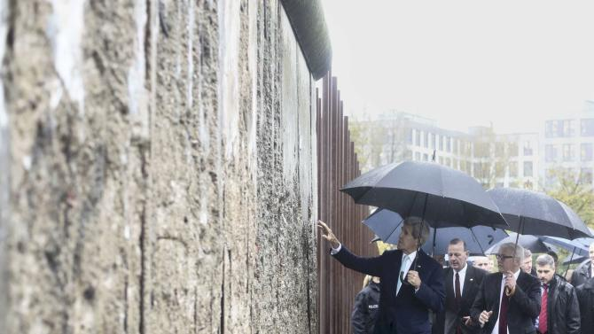 United States Secretary of State Kerry touches remains of the Berlin Wall during a visit at the Wall memorial site