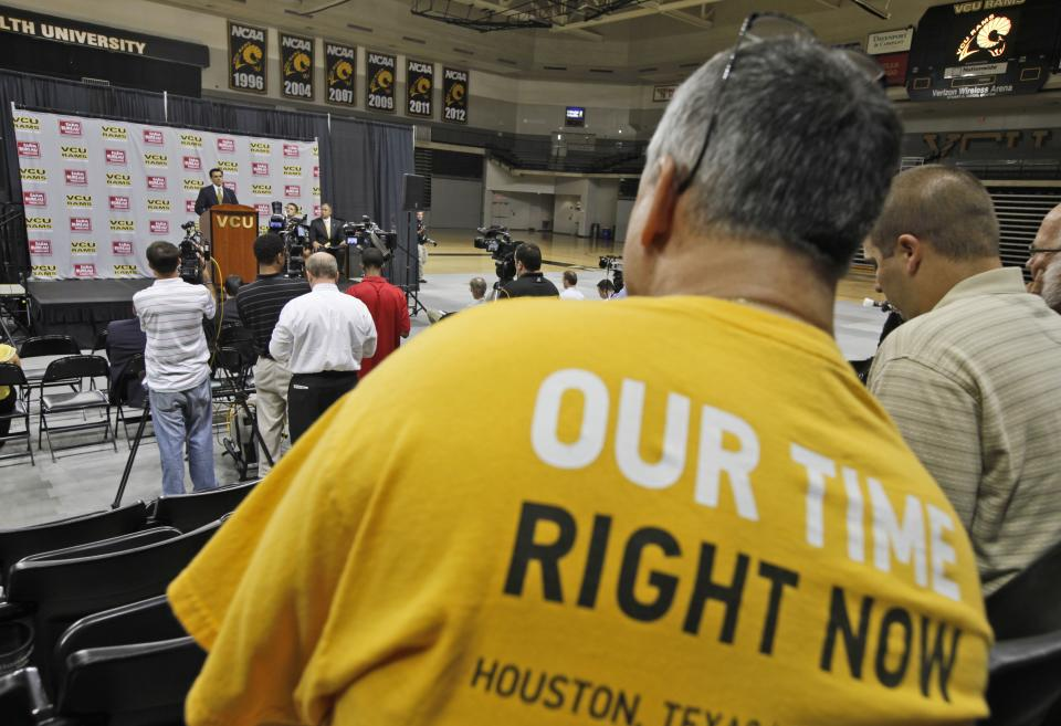 A Virginia Commonwealth University fan wears a VCU tee-shirt during a news conference as VCU president Michael Rao speaks in Richmond, Va., Tuesday, May 15, 2012. Rao announced that VCU would join the Atlantic 10 conference in June. (AP Photo/Steve Helber)
