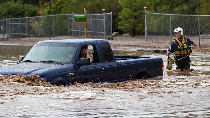 A man an woman sit in a truck on Tomahawk Rd. flooded by rain waters in Apache Junction, Ariz., Sunday, July 21, 2013. Mesa Fire Dept. were able to walk the two out safely. (AP Photo/The Arizona Republic, Michael Chow)