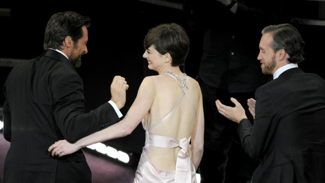 """Hugh Jackman, left, and Adam Shulman, right, congratulate Anne Hathaway after she was announced as winner of the award for best actress in a supporting role for """"Les Miserables"""" during the Oscars at the Dolby Theatre on Sunday, Feb. 24, 2013, in Los Angeles. (Photo by Chris Pizzello/Invision/AP)"""