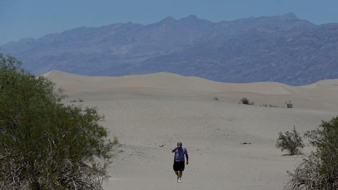 Dan Kail, 67, of Pittsburg Pa., walks thru the sand dunes in Death Vally National Park Friday, June 28, 2013 near Stovepipe Wells, Calif. Excessive heat warnings will continue for much of the Desert Southwest as building high pressure triggers major warming in eastern California, Nevada, and Arizona. (AP Photo/Chris Carlson)