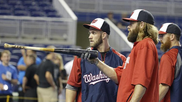 Washington Nationals left fielder Bryce Harper, left, talks with right fielder Jayson Werth, center, during batting practice before a baseball game against the Miami Marlins, Monday, July 28, 2014, in Miami. (AP Photo/Lynne Sladky)