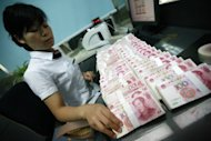 A Chinese bank staff counts the stacks of 100-yuan notes at a bank in Huaibei, China, on June 8. The G20 group of the world&#39;s major economic powers will welcome China&#39;s decision to allow the value of the yuan to move more freely, according to a draft summit statement