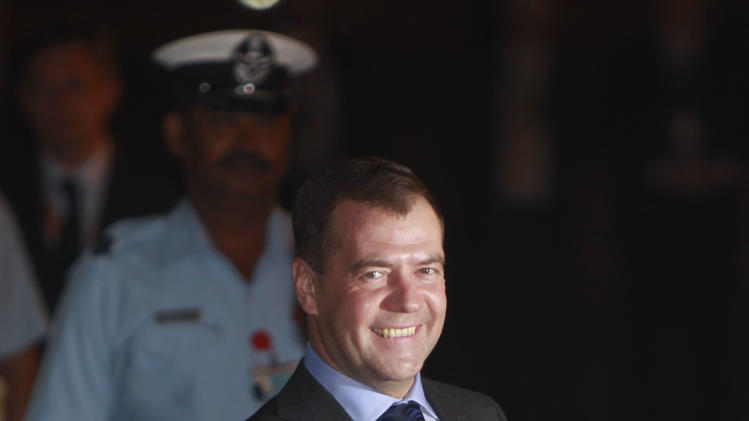 Russian President Dmitry Medvedev smiles upon arrival at the Palam Technical Airport in New Delhi, India, Wednesday, March 28, 2012. Medvedev is in India attending the BRICS (Brazil, Russia, India, China, South Africa) Summit which is to be held March 29 in New Delhi. (AP Photo/Mustafa Quraishi)