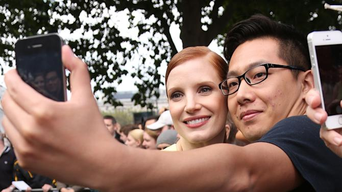 A fan takes a photograph with US actress Jessica Chastain as she arrives for the Salome and Wild Salome UK Premiere at the BFI Southbank in central London, Sunday, Sept. 21, 2014. Salome and Wild Salome, based on Oscar Wilde's play, was presented together followed by a Q&A with Al Pacino and Jessica Chastain hosted by Stephen Fry, and broadcast live to cinemas around the country. (Photo by Joel Ryan/Invision/AP)