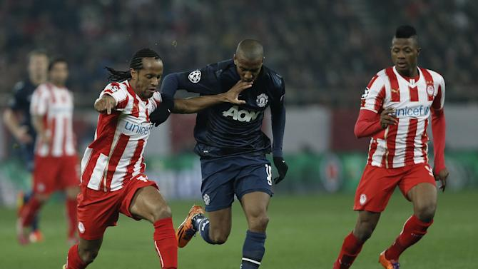 Olympiakos' Leadro Salino, left, fights with Manchester United's Ashley Young during their Champions League, round of 16, first leg soccer match at Georgios Karaiskakis stadium, in Piraeus port, near Athens, on Tuesday, Feb. 25, 2014