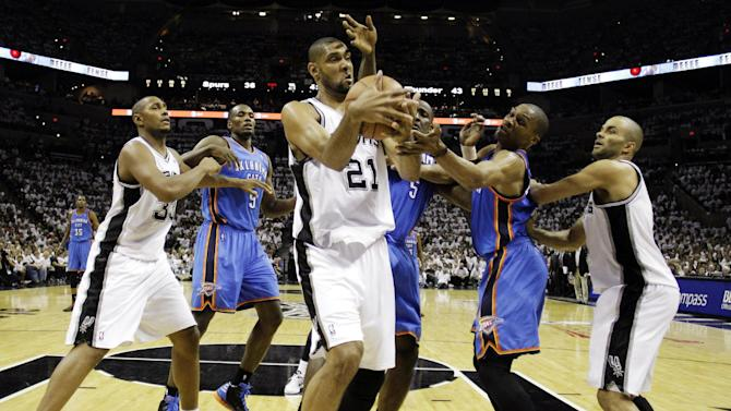 San Antonio Spurs center Tim Duncan (21) grabs a rebound as Oklahoma City Thunder center Kendrick Perkins (5) and point guard Russell Westbrook defend during the first half of Game 5 in the NBA basketball Western Conference finals, Monday, June 4, 2012, in San Antonio. Spurs power forward Boris Diaw (33), of France, Thunder power forward Serge Ibaka (9), from the Republic of Congo, and Spurs point guard Tony Parker, left, of France, watch the action. (AP Photo/Eric Gay)