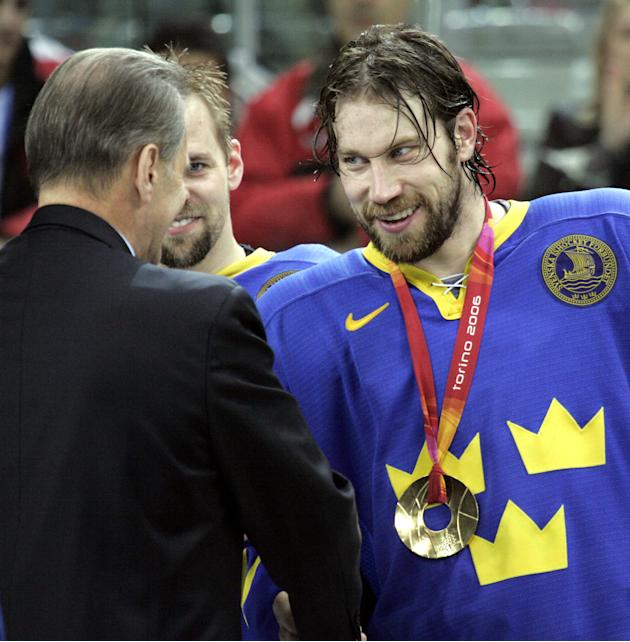 FILE - In this Feb. 26, 2006 file photo, IOC president Jacques Rogge, left, shakes hands with Sweden's Peter Forsberg during the medal ceremony afte Sweden beat Finland 3-2 in the 2006 Winter Olympics