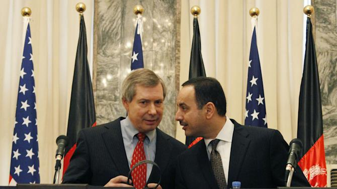 Eklil Hakimi, right, Afghanistan's ambassador in Washington, whispers to James Warlick, the U.S. deputy special representative for Afghanistan and Pakistan during a joint press conference in Kabul, Afghanistan, Thursday, Nov. 15, 2012. The United States and Afghanistan are starting negotiations on an agreement that will shape America's military presence in the country after the withdrawal of most foreign combat troops at the end of 2014. (AP Photo/Ahmad Jamshid)