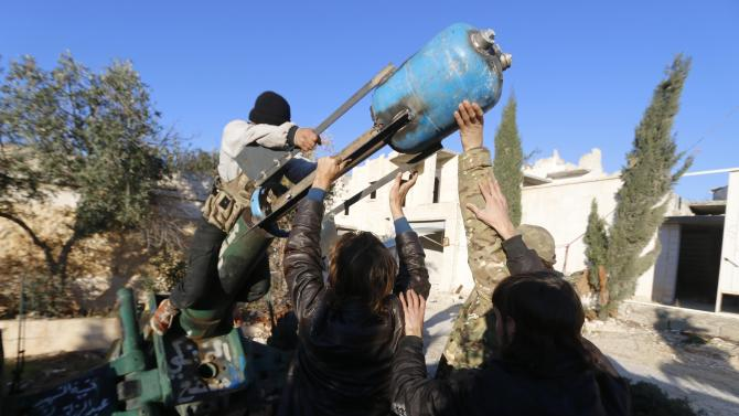 Fighters from the Noureddine Zanki movement prepare an improvised explosive to fire towards forces loyal to Syria's President al-Assad at the frontline in Aleppo