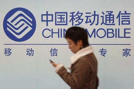 A woman looks at the screen of her mobile phone while walking past a China Mobile sign in downtown Shanghai