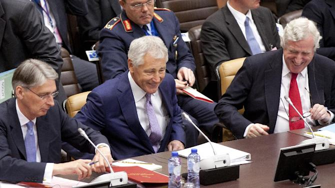 From left, British Defense Minister Philip Hammond, U.S. Defense Secretary Chuck Hagel and EU representative to NATO Pierre Vimont speak with each other during a round table meeting of NATO defense ministers and non NATO ISAF member nations at NATO headquarters in Brussels on Wednesday, June 5, 2013. NATO defense ministers are expected to agree Wednesday on the cornerstones of the alliance's operations in Afghanistan after its combat mission ends in 2014, during a second day of talks in Brussels. (AP Photo/Virginia Mayo)