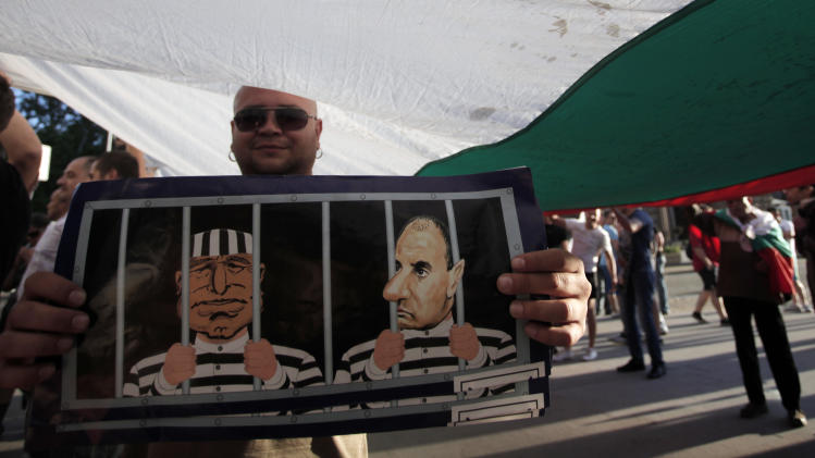 A demonstrator shows a poster depicting former PM Boyko Borisov and his vice-president Tsvetan Tsvetanov behind bars during a protest against the center-right GERB party in Sofia, Saturday, May 11, 2013. 350,000 illegally printed ballots were seized just hours before the start of parliamentary elections. Vote-buying and other election fraud concerns have prompted the Organisation for Security and Cooperation in Europe (OSCE) to dispatch its biggest monitoring mission to Bulgaria since 1990 for Sunday's vote. (AP Photo/Valentina Petrova)