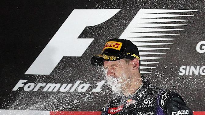 Red Bull driver Sebastian Vettel of Germany is sprayed in the face with champagne as he celebrates on the podium after winning the Singapore Formula One Grand Prix on the Marina Bay City Circuit in Singapore, Sunday, Sept. 22, 2013