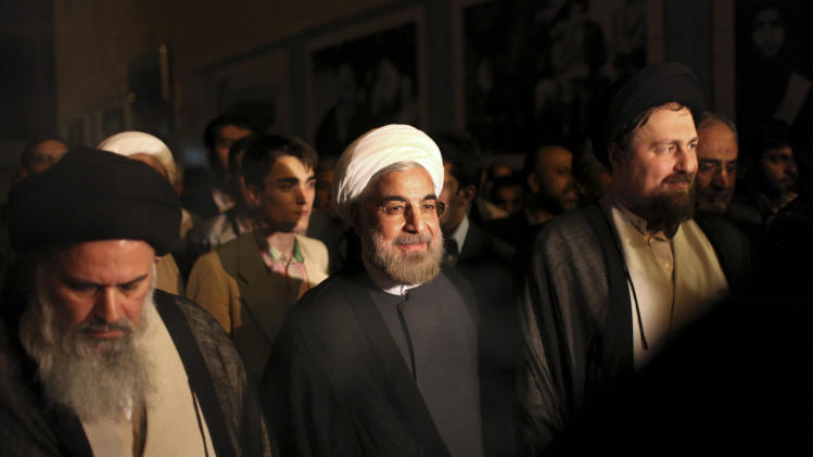 """Iranian President elect Hasan Rowhani, center, is accompanied by Hasan Khomeini, grandson of the late revolutionary founder Ayatollah Khomeini, right, and Ayatollah Mousavi Bojnourdi, during visit of Ayatollah Khomeini's shrine, just outside Tehran, Iran, Sunday, June 16, 2013. Iran's newly elected reformist-backed president Hasan Rowhani said Sunday that the country's dire economic problems cannot be solved """"overnight,"""" as he took his first steps in consulting with members of the clerically dominated establishment on his new policies.(AP Photo/Ebrahim Noroozi)"""