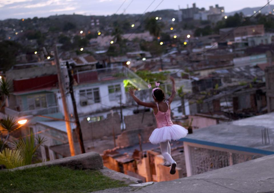 A girl wearing a ballet dress plays on the street in Santiago de Cuba, Cuba, Sunday, March. 25, 2012. (AP Photo/Ramon Espinosa)