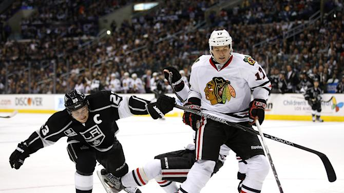Los Angeles Kings' Dustin Brown, left, extends his stick to slow Chicago Blackhawks' Sheldon Brookbank, right, during the second period of an NHL hockey game in Los Angeles, Saturday, Jan. 19, 2013. (AP Photo/Jae C. Hong)