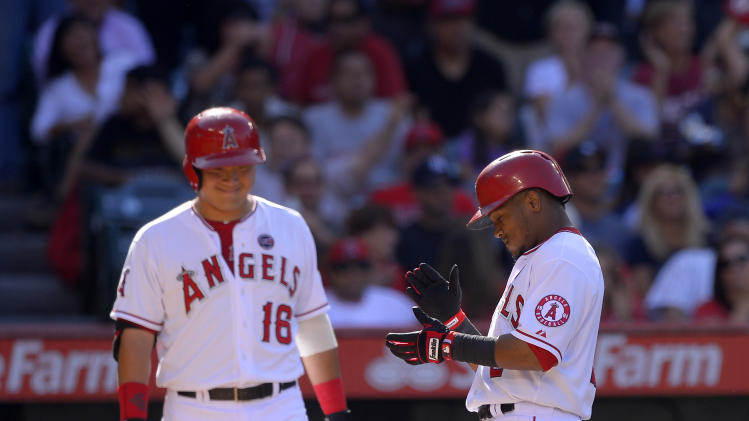 Los Angeles Angels' Erick Aybar, right, steps on home plate after hitting a solo home run as teammate Hank Conger looks on during the second inning of their baseball game against the New York Yankees, Saturday, June 15, 2013, in Anaheim, Calif. (AP Photo/Mark J. Terrill)