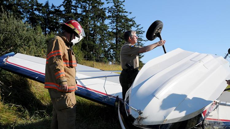 "In this Friday, Aug. 31, 2012 photo provided by the San Juan Islander, authorities examine a plane, piloted by author Richard Bach, that crashed in a field in Friday Harbor, Wash. Bach, the author of the 1970s best-selling novella ""Jonathan Livingston Seagull"" among other spiritually oriented writings often rooted in themes of flight, was in serious condition Saturday at Harborview Medical Center. (AP Photo/San Juan Islander, Matt Pranger) MANDATORY CREDIT"