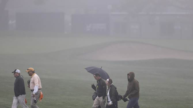 Golf fans cross a fairway in the fog at Torrey Pines golf course during a weather delay before the start of the third round of the Farmers Insurance Open golf tournament  Saturday, Jan. 26, 2013, in San Diego. (AP Photo/Lenny Ignelzi)