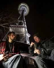 Dustin, left, and Paul of Tacoma, Washington, share a water pip underneath the Space Needle shortly after a law legalizing the recreational use of marijuana took effect on December 6, in Seattle, Washington. Voters approved an initiative to decriminalize the recreational use of marijuana making it one of the first states to do so