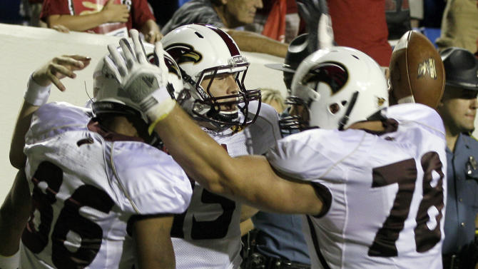Louisiana Monroe quarterback Kolton Browning, center, celebrates with teammates Je'Ron Hamm (86) and Jon Fisher (78) after Browning scored the winning overtime touchdown to defeat Arkansas 34-31 in an NCAA college football game in Little Rock, Ark., Saturday, Sept. 8, 2012. (AP Photo/Danny Johnston)