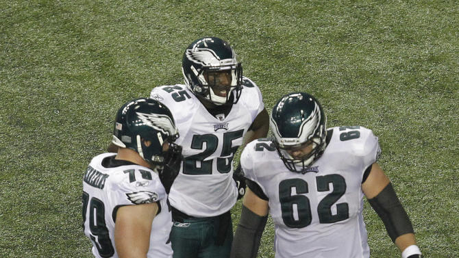 Philadelphia Eagles quarterback Michael Vick (7) lies injured on the field as teammates Clay Harbor (82), LeSean McCoy (25) and tackle Todd Herremans (79) stand over him in the second half of an NFL football game at the Georgia Dome in Atlanta on Sunday, Sept. 18, 2011. (AP Photo/Butch Dill)