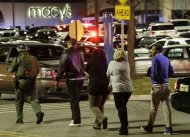 An official, left, wearing tactical gear leads a group of people out of the Garden State Plaza Mall during a lockdown following reports of a shooter, Tuesday, Nov. 5, 2013, in Paramus, N.J. (AP Photo/Julio Cortez)