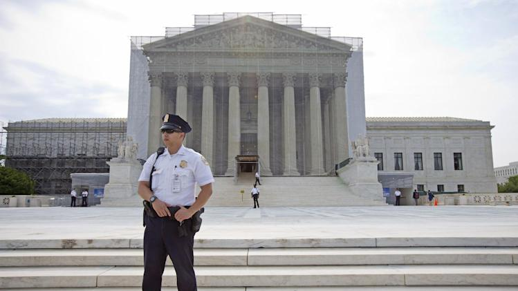 A police officer keeps watch outside the Supreme Court in Washington, Monday, June 17, 2013. With a week remaining in the current Supreme Court term, several major cases are still outstanding that could have widespread political impact on same-sex marriage, voting rights, and affirmative action. (AP Photo/J. Scott Applewhite)