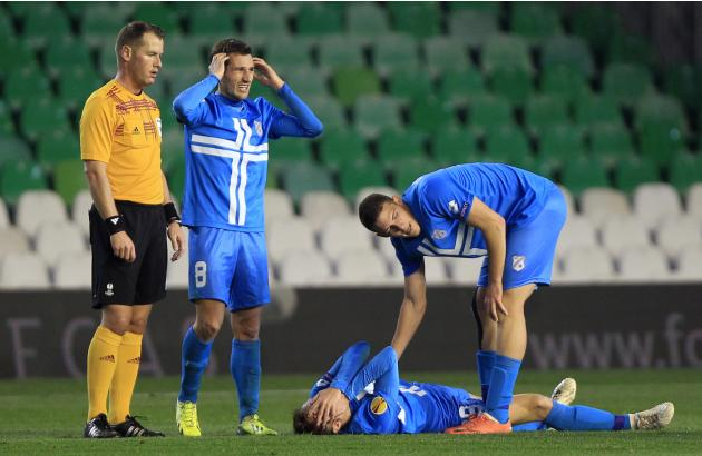 Rijeka's Jugovic lies on the pitch as he bleeds during their soccer match against Real Betis in Seville