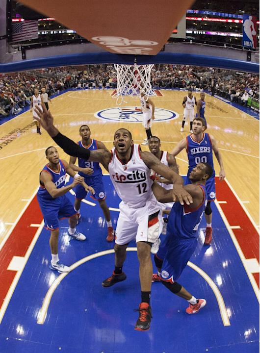 Portland Trail Blazers' LaMarcus Aldridge, center, reacts to his shot as Philadelphia 76ers' Thaddeus Young, right of center, guards him during the first half of an NBA basketball game on Satu