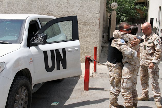 UN observers welcome their comrades upon their return from al-Haffa, in northern Syria, to Damascus, Syria on Saturday, June 16, 2012. U.N. Observers in Syria suspended their activities and patrols Saturday because of escalating violence in the country, the head of the mission said, the strongest sign yet that an international peace plan for Syria is disintegrating. (AP Photo/Bassem Tellawi)