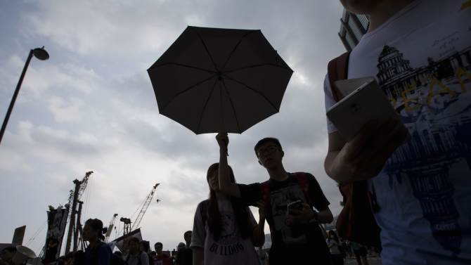 A student protester holds up a umbrella during a rally outside the Golden Bauhinia square, venue of the official flag-raising ceremony for celebrations of China's National Day, in Hong Kong
