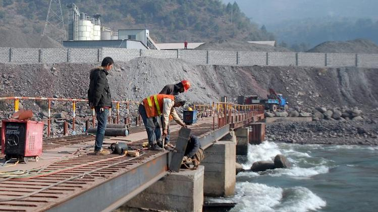 A Chinese engineer (L) supervises workers building a bridge over a river in Ghari Dopatta, in Pakistan, December 6, 2013