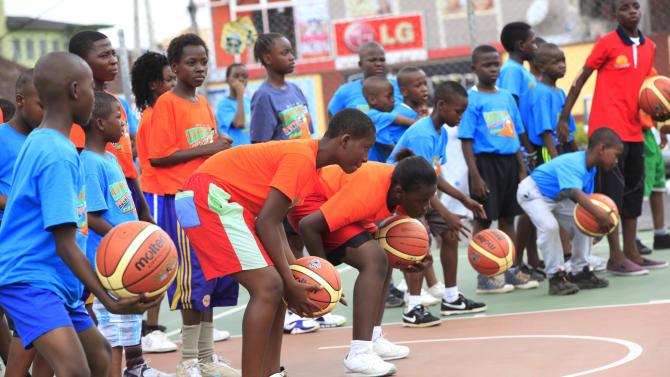 "In this photo taken Tuesday, Sept . 10, 2013, children learn passes and basic moves during a basket ball camp organized by former Seattle Supersonics and Orlando Magic center Olumide Oyedeji, in Lagos, Nigeria. About 30 years after NBA Hall of Famer Hakeem ""The Dream"" Olajuwon first emerged from the sprawling city of Lagos, basketball is gaining momentum in this West African country of nearly 160 million people which, like most of the continent, has had little space for any sport other than soccer. (AP Photo/Sunday Alamba)"