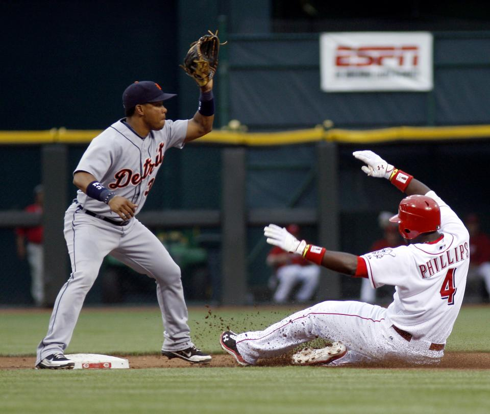 Cincinnati Reds' Brandon Phillips (4) slides safely into second base for a double beating the tag from Detroit Tigers shortstop Ramon Santiago in the second inning of a baseball game, Sunday, June 10, 2012, in Cincinnati. (AP Photo/David Kohl)