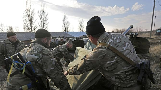 Ukrainian servicemen cover a canon as Ukrainian armored vehicles with canons in tow are parked in the town of  Druzhkivka, east Ukraine, Friday, Feb. 27, 2015. Ukrainian and Russian-backed separatist forces have begun drawing back heavy weapons from the front line separating them in compliance with a cease-fire deal agreed in Belarus earlier in the month. (AP Photo/Sergei Chuzavkov)